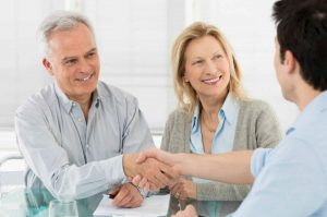 A happy couple shakes a man's hand over paperwork